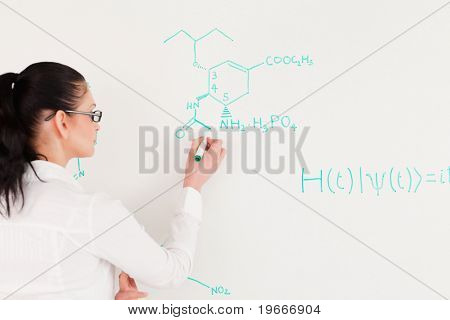 Scientist writing a formula on a white board