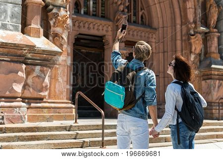 Young couple with pack-sacks are standing near entrance to old gothic building. They are making selfie by cellphone and holding hands. Focus on back. Copy space in left side