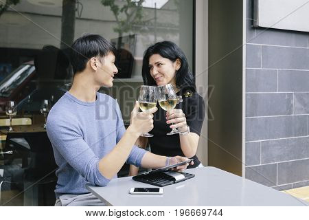 Multiethnic couple toasting with a glass of wine in a restaurant