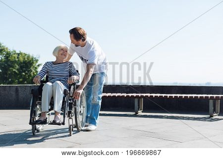 Take good care of yourself. Handsome kind attentive man making sure elderly lady doing fine while they taking daily stroll around the park