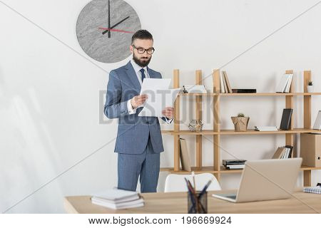 Focused Businessman In Grey Suit Analyzing Documents In Modern Office