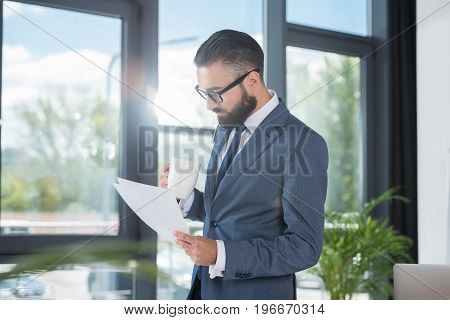 Side View Of Businessman With Coffee Cup In Hand Analyzing Papers In Office