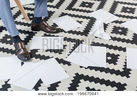 partial view of businessman legs and empty papers on floor in office