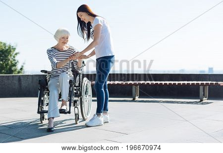 Step by step. Stunning incredible devoted woman trying standing up from her wheelchair while young volunteer making sure she not being injured