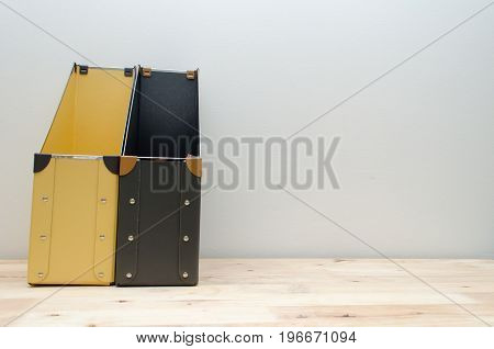 black and yellow blank office document file folders stack on wooden desk with white wall background business concept