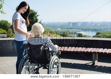 I am here if you need me. Dedicated emotional stunning volunteer making senior woman feeling better while supporting her and taking her for a daily stroll in the park