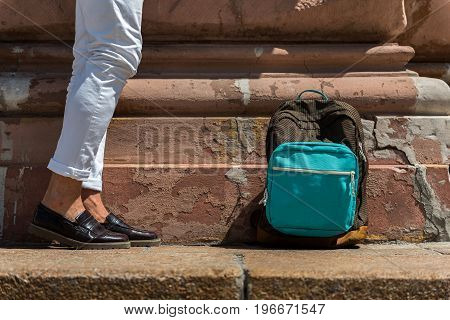 Close up of legs and pack-sack of youthful guy standing hip to uneven wall of old construction. Bag is lying on stone sidewalk