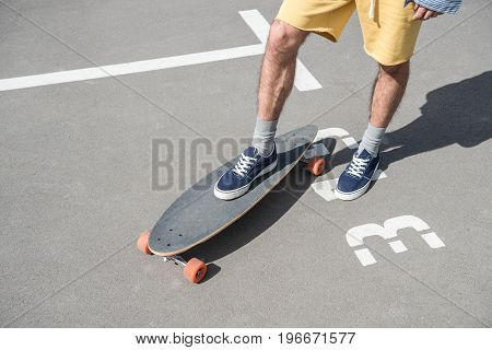 cropped shot of man in shorts standing on longboard on street