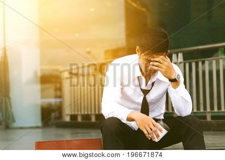 Business asian man sitting front company and stressed or worried bout resistance of work.