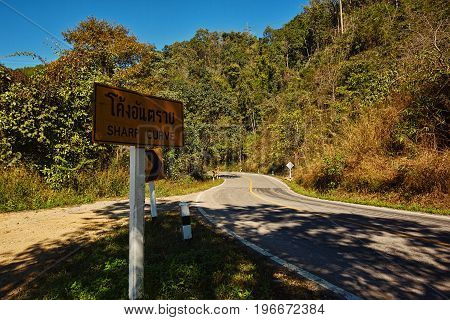 MAE HONG SON PROVINCE THAILAND - JANUARY 14 2017: Sharp curves on serpentine road with warning road sign
