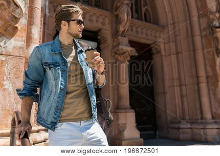 Serious young bearded guy with computer bag is standing beside building of old architecture. He is touching rail and holding coffee cup, looking aside through sunglasses. Copy space in right side