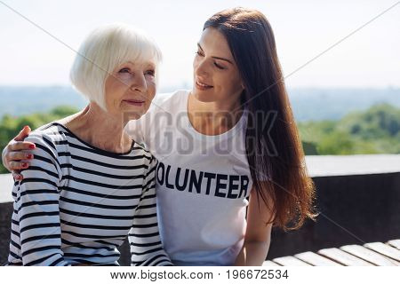 Dreaming about the past. Dedicated observant passionate volunteer making sure elderly woman feeling while taking her for a daily walk and enjoying warm weather with her