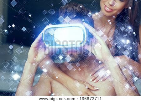 Young man with VR headset and girlfriend enjoying cyberspace blue glowing tiles