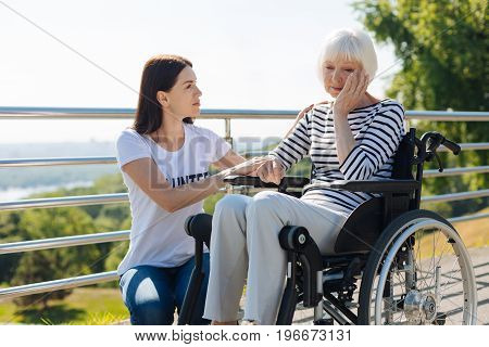 What is the matter. Enchanting committed pretty volunteer supporting senior lady who suffering from leg injury and providing her assistance until her recovery