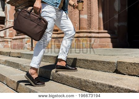 Close up of legs and hands of youthful guy scaling stone steps of old architecture building. He is carrying bad and cup of coffee