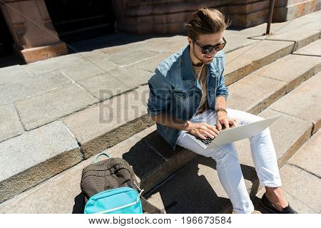 Top view of young bearded guy in sunglasses sitting on slab steps outside city building. He is holding notebook on laps and typing something with smile