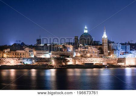 Blue hour on Malta's capital city Valletta shot from across the port in Saint Julian.