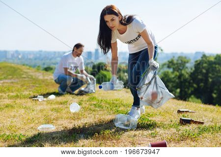 Eco enthusiast. Young motivated intelligent lady working as a volunteer and participating in environmental initiative while collecting litter in the park
