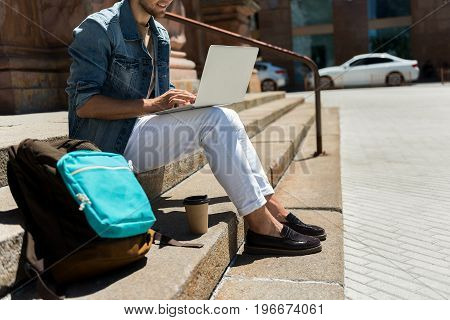 happy youthful bearded man sitting on steps of old city building. He is typing on notebook on his lap. Backpack and coffee cup standing on stairs nearby