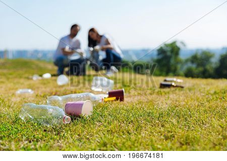 Neutralizing pollution. Active devoted progressive people participating in eco campaign and collecting litter in the park while being enthusiastic the environment