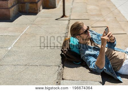 Serious young man with beard is lying on street steps and writing message on his mobile phone. He is leaning shoulders on his pack-sack. Copy space in left side