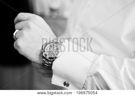 Handsome Groom Dressing Up In His Room For His Wedding Ceremony. Black And White Photo.