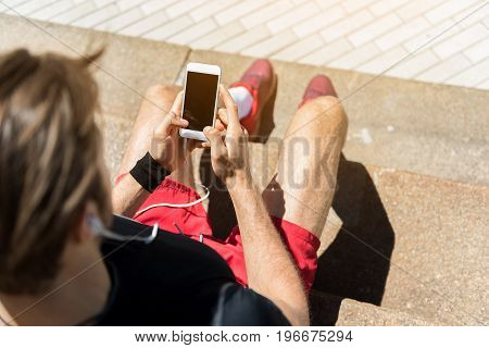 Top view of young man in sportswear sitting on stairs outside. He is holding mobile and listening to music via earphones. Focus on smartphone