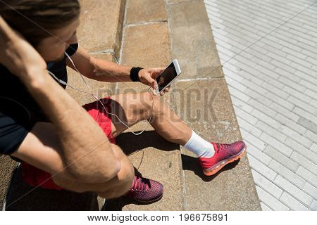 Close up of hands and legs of young sportsman sitting on street stairs. He is listening to music via smartphone. Top view