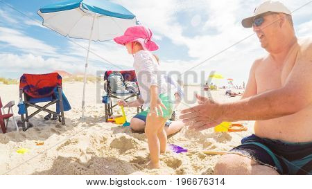 Myrtle Beach South Carolina USA-July 11 2017. POV point of view - Summer vacation on the beach. Father and kids playing in the sand.