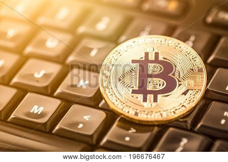 Bitcoin gold coin on computer keyboard. Virtual cryptocurrency concept.