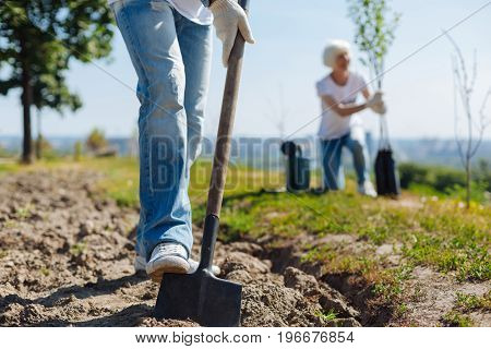 Mens work. Productive diligent motivated guy digging holes for new plants while participating in local eco campaign and being enthusiastic about environment