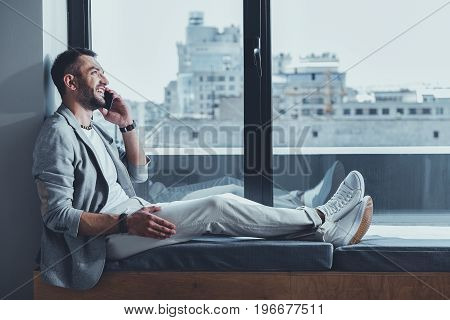 Good news. Fashionable joyful guy is enjoying pleasant conversation using smartphone. He is sitting on windowsill against cityscape and expressing gladness. Copy space in the right side