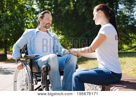 Psychological aid. Devoted brilliant genuine volunteer talking to a gentleman who sitting in a wheelchair and encouraging him working on his rehabilitation