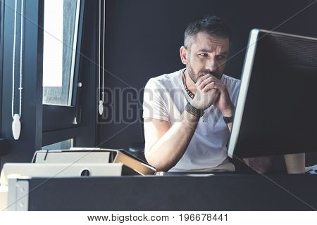 Work issues. Nervous middle-aged employee is working on computer with concentration and expressing disappointment while looking at screen thoughtfully and touching his chin. Copy space in left side