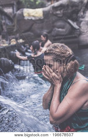 European woman at Pura Tirta Empul temple during a religious ceremony in Tampa, Bali.