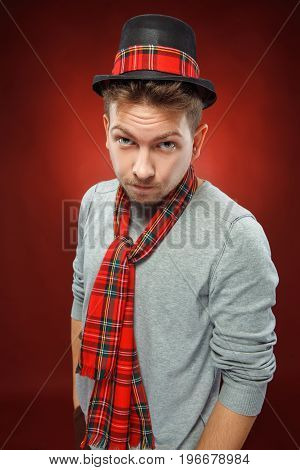 The young man in cap looking at camera on red background