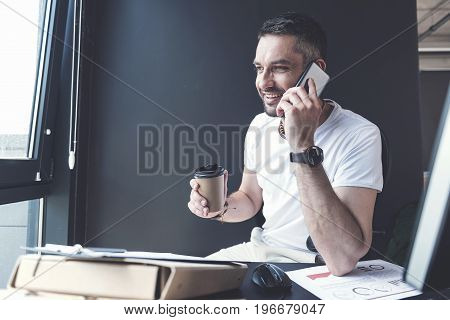 Pleasant conversation. Portrait of happy manager is sitting at his workplace with espresso while talking on mobile phone and expressing joy. He is looking aside with smile. Copy space in the left side