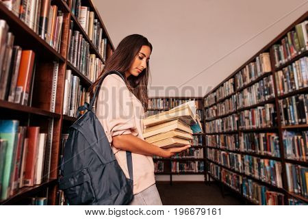 Young female student carrying lots of books in the college library. Caucasian student reading books in library.