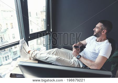 Enjoying beverage. Profile of joyful adult manager is resting in his chair while drinking coffee and looking at cityscape through window with smile. Copy space in the left side
