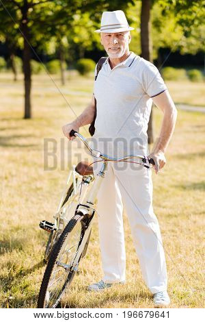 Be like a model. Attractive male person wearing stylish hat and expressing positivity while holding handle bar