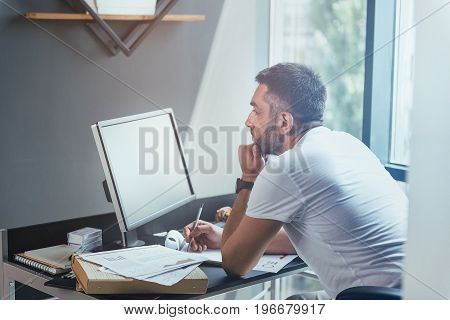 Serious bristled employee is working hard in office. He is sitting at his workplace and working on computer with concentration