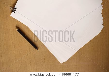 White paper and pen on the wooden table.
