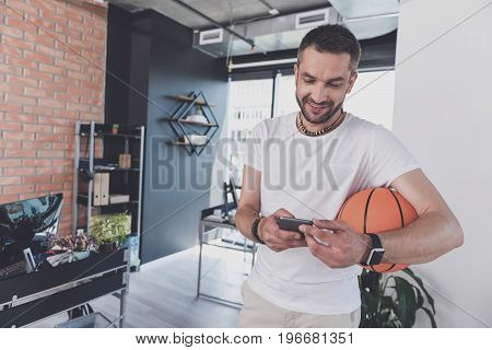 Enjoying pause in work. Joyful bristled man is standing in modern office and holding basketball and smartphone. He is expressing gladness while typing message on gadget. Copy space in the left side