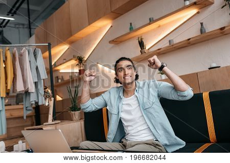 Triumphing Young Man Using Laptop And Looking Away In Boutique