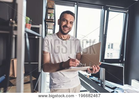 Involved in project. Portrait of glad bearded employee is leaning on shelf and looking at camera with joy. He is holding opened folder with documents and going to make note. Big window on background