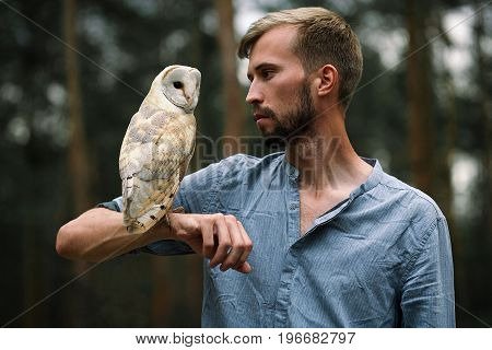 Portrait of young man in blue shirt with owl in forest. Owl sits on his hand and guy looks at the owl. Close-up.