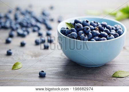 Small Bowl of Organic Blueberries on Wooden Table. Fresh blueberries in a small bowl on a rustic wooden table.