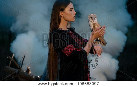 Girl with long hair in red and black dress stands with owl on her hand in forest against smoke background. Owl is tied to her arm by chain.