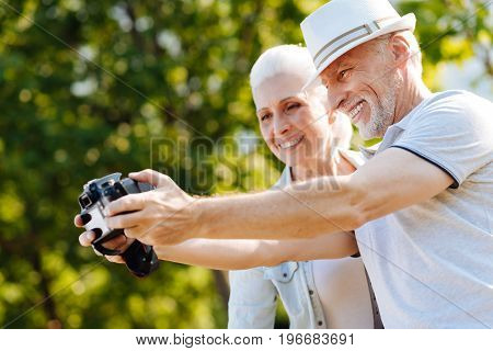 Taking picture. Attractive male person standing in semi position and holding camera in both hands while looking forward