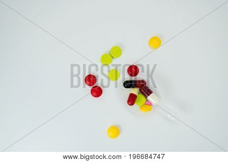 Colorful tablets in teaspoon and many pills spread on a white background